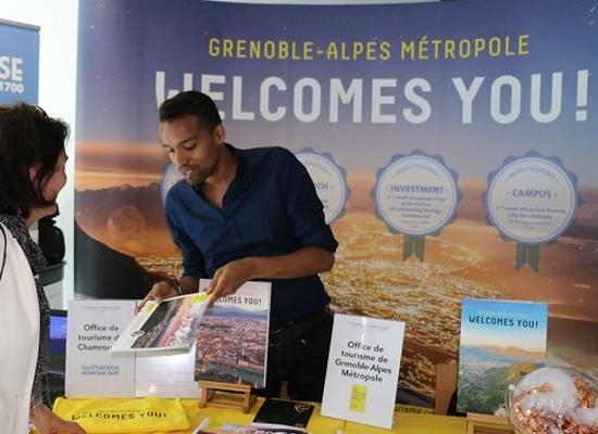 Deux personnes en discussion devant le stand Grenoble Alpes Métropole