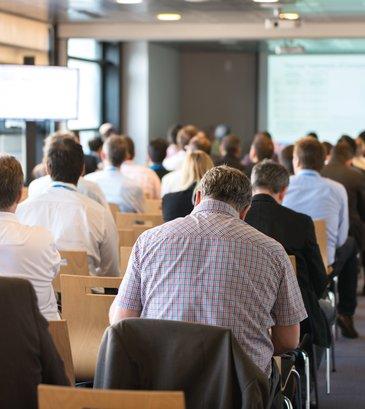 Personnes assises dans une salle de séminaire écoutant une conférence