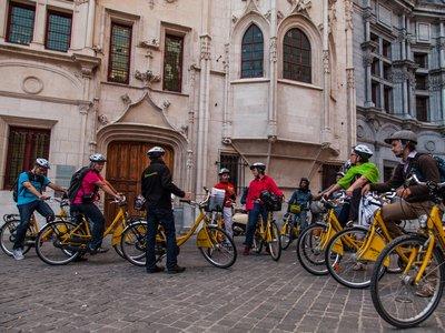 Visiteurs à vélo devant l'ancien palais du parlement
